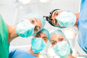 Hospital - surgery medical team of doctors in operation room or