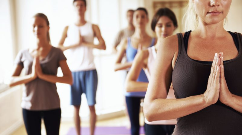 Placid yoga class members standing in meditation during a session